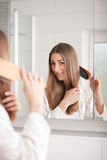 Young woman brushing hair in front of mirror Stock Photography