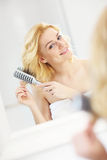 Young woman brushing hair Stock Image