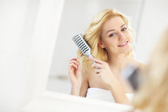 Young woman brushing hair Stock Photos