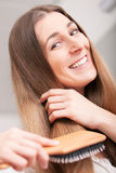 Young woman brushing her hair Royalty Free Stock Images