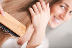 Young woman brushing her hair Stock Photography
