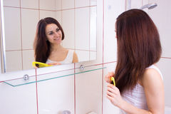 Young woman brushing her hair in bathroom Stock Images