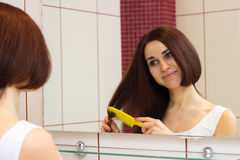 Young woman brushing her hair in bathroom Stock Image