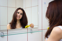 Young woman brushing her hair in bathroom Stock Photos