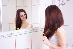 Young woman brushing her hair in bathroom Royalty Free Stock Images