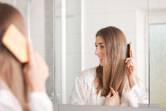 Young woman brushing her hair in front of the mirr Stock Photo