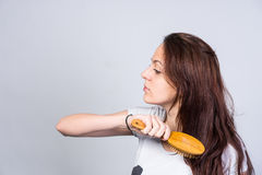 Young woman brushing her long brown hair Stock Image