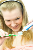 Young woman brushing her teath. Young blond woman applies toothpaste to brush her teeth Stock Images