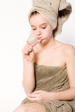 Young woman is brushing her teeth. Young woman in towel on a white background brushing her teeth Royalty Free Stock Photos