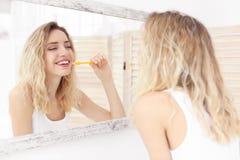 Young woman brushing her teeth. In bathroom Stock Photo