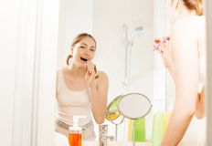 Young woman brushing her teeth in the bathroom Stock Photo