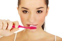 Young woman brushing her teeth. Young beautiful woman brushing her teeth Stock Image