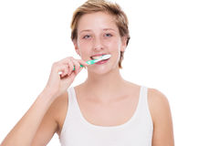 Young woman brushing her teeth. Young blonde woman brushing her teeth with a toothbrush on white background Royalty Free Stock Photo