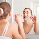 Young woman brushing her teeth in front of a mirro Stock Images