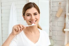 Young woman brushing her teeth. Indoors Stock Images