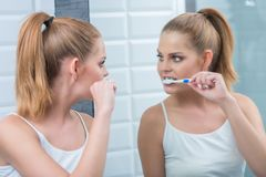 Young woman brushing her teeth in the mirror Stock Images
