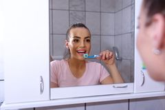 Young woman brushing her teeth at mirror. In bathroom royalty free stock images