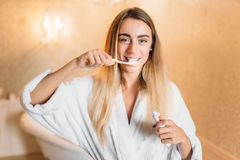 Young woman brushing her teeth with toothbrush Royalty Free Stock Photography