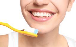 Young woman brushing her teeth. On white background, closeup Stock Images