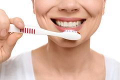 Young woman brushing her teeth on white background. Closeup Stock Photos