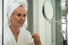 Young woman brushing teeth against mirror. Young blonde woman with towel on head and wearing bathrobe brushing teeth against mirror in bathroom stock images