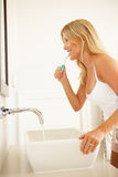 Young Woman Brushing Teeth In Bathroom Stock Photo