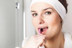 Young woman brushing teeth. Beautiful young woman with green eyes brushing teeth royalty free stock image