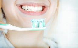 Young woman brushing teeth . Stock Photography