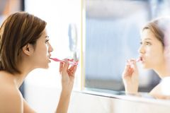 Woman brushing teeth and looking in the mirror. Young woman brushing teeth and looking in the mirror Royalty Free Stock Photos
