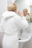 Young woman brushing teeth and looking at mirror in bathroom. Young beautiful woman brushing teeth and looking at mirror in bathroom royalty free stock image