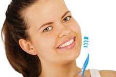 Young woman brushing teeth over white backgrund. Smiling showing white teeth`s Stock Image