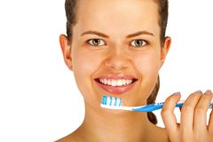 Young woman brushing teeth over white backgrund. Smiling showing white teeth`s Royalty Free Stock Images