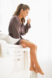 Young woman brushing teeth while sitting in bathroom Stock Photos