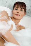 Young woman in bubble bath. Focus on face royalty free stock image