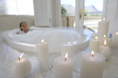 Young woman in bubble bath, illuminated candles in foreground Royalty Free Stock Photos