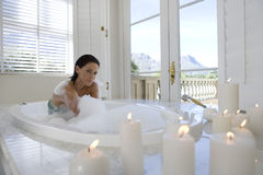 Young woman in bubble bath, portrait, illuminated candles in foreground royalty free stock photo