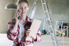 Young woman builder, architect, designer dressed in shirt and glasses is standing in workshop, talking on cell phone. And holding clipboard. In background Royalty Free Stock Photo