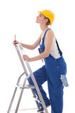Young woman builder in blue coveralls with screwdriver on ladder Stock Images