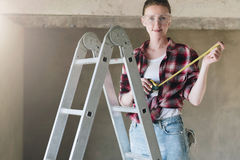 A young woman builder, dressed in a plaid shirt, blue jeans and construction glasses, stands on a stepladder. And holds roulette in her hands. Construction Royalty Free Stock Image