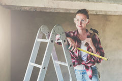 A young woman builder, dressed in a plaid shirt and construction glasses, stands on a stepladder and holds roulette Royalty Free Stock Images