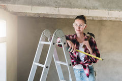 A young woman builder, dressed in a plaid shirt and construction glasses, stands on a stepladder and holds roulette Royalty Free Stock Photos