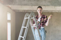 A builder, dressed in a plaid shirt and construction glasses, stands on a stepladder and holds roulette in her hands. A young woman builder, dressed in a plaid Royalty Free Stock Photo