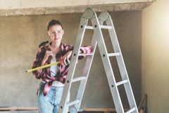 A young woman builder, dressed in a plaid shirt and construction glasses, stands in the workshop on a stepladder. And holds a roulette and a hammer in her hands Royalty Free Stock Photos