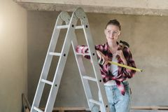 A young woman builder, dressed in a plaid shirt and construction glasses, stands in the workshop on a stepladder. And holds a roulette and a hammer in her hands Stock Image
