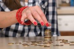 Young woman building coin-stacks. Close Up Stock Photos