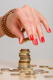 Young woman building coin-stacks Royalty Free Stock Photo