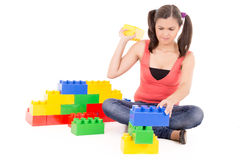 Young woman building with colorful blocks Royalty Free Stock Photos