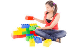 Young woman building with colorful blocks Royalty Free Stock Photography