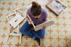 Young woman building piece of furniture Royalty Free Stock Images