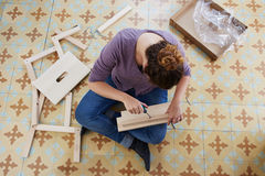 Young woman building piece of furniture Stock Image
